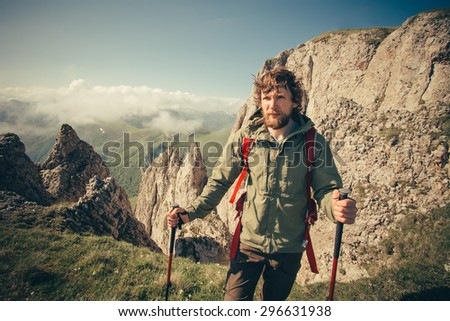 Young Man with backpack hiking outdoor Travel Lifestyle survival concept with rocky mountains on background Summer vacations