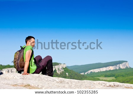 Young man with backpack sitting on cliff and looking to a view