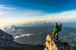 Young man with backpack standing on a cliffs edge on the top of mountain with gorgeous view to forests, clouds and sea. Volcano Agung, Bali, Indonesia.