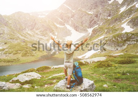 Young man with backpack standing with raised hands on the mountain and enjoying valley view #508562974