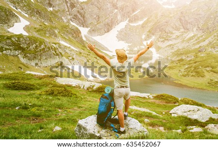 Young man with backpack standing with raised hands on the mountain and enjoying valley view #635452067