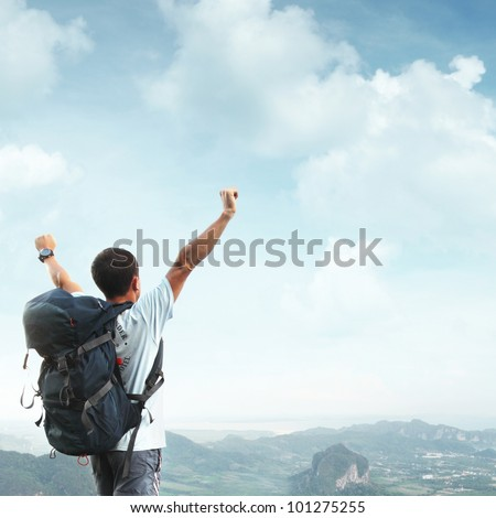 Young man with backpack standing with raised hands on top of a mountain and enjouing valley view