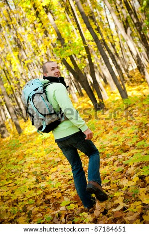Young man with backpack walking through autumn forest