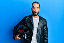 Young man with beard holding motorcycle helmet scared and amazed with open mouth for surprise, disbelief face