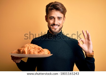 Young man with beard holding plate with croissants standing over isolated yellow background doing ok sign with fingers, excellent symbol Stock fotó ©