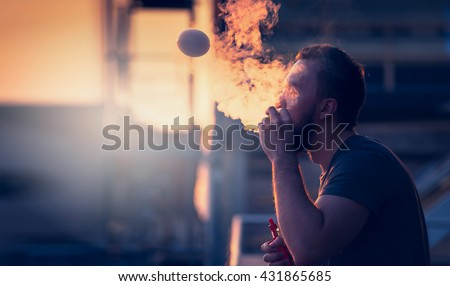 young man with beard on blurry background sunset sky, making soap bubbles with smoke inside with the aid of vape