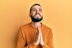 Young man with beard wearing casual winter sweater begging and praying with hands together with hope expression on face very emotional and worried. begging.
