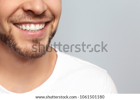 Young man with beautiful smile on grey background. Teeth whitening