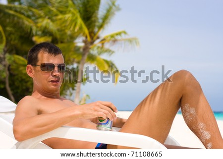 Young man with beer on a tropical beach