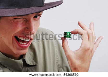 Young man with blinking eye and game cube on six