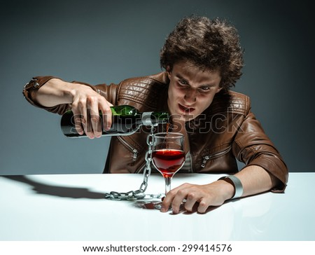 Young man with bottle of alcohol / photo of youth addicted to alcohol, alcoholism concept, social problem
