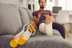Young man with broken leg in plaster cast sitting on sofa and using tablet computer. Close up of foot and crutches. Physical injury, bone fracture, treatment and rehabilitation at home concept