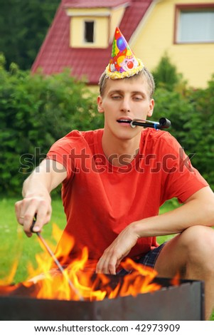 stock photo : young man with calumet near brazier on picnic, happy birthday party