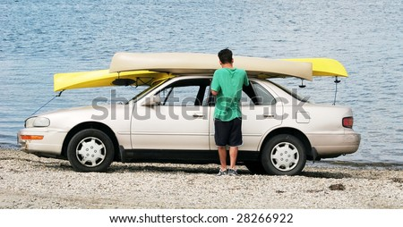 young man with canoes on top of car