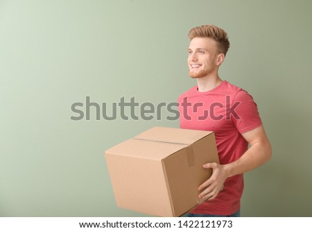 Young man with cardboard box on color background