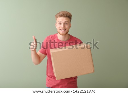 Young man with cardboard box showing thumb-up on color background