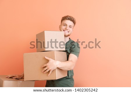 Young man with cardboard boxes on color background