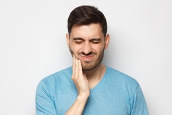 Young man with closed eyes suffering from severe toothache, touching jaw with fingers trying to ease strong tooth pain, isolated on gray background