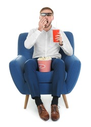 Young man with 3d glasses and drink eating popcorn while sitting in armchair during cinema show on white background