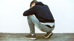 Young man with depression and drug addiction (artificial, dreary colored) in hoodie.