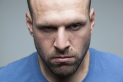 Young man with diabolical facial expression and squinting eyes,stubble five o'clock shadow beard,sexy attractive prison felon inmate headshot,isolated on neutral gray background,close up portrait