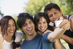 Young man with digital camera photographing himself and three friends