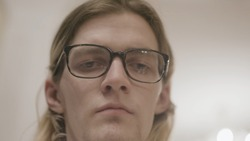 Young man with downcast eyes. Stock. Close-up of young man with glasses with drooping look and tired look. Hipster in glasses with indifferent drooping look