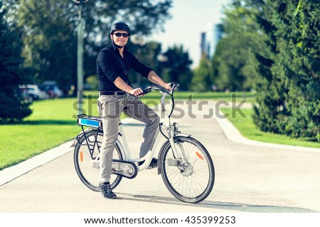 Young man with electric bicycle or E-bike