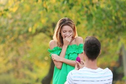 Young man with engagement ring making proposal of marriage to his girlfriend in park