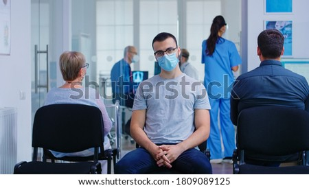 Young man with face mask against coronavirus looking at camera in hospital waiting area. Senior woman with walking frame waiting for consultation in clinic. Foto stock ©