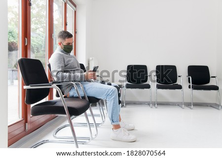 Young man with face mask sitting in a waiting room of a hospital or office looking at smartphone - focus on the man Foto stock ©