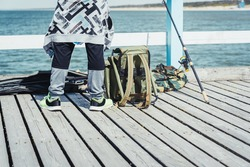 Young man with fishing rod on the Baltic sea pier. People leisure hobby concept.