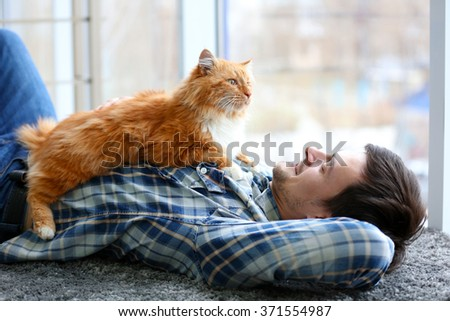 Young man with fluffy cat lying on a carpet