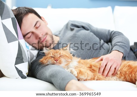 Young man with fluffy cat lying on a sofa