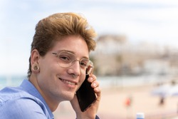 Young man with glasses and piercings talking with a mobile while is smiling and turning the face