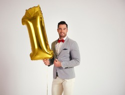 Young man with golden balloon celebrating first birthday his company