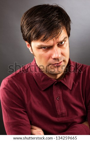Young man with grumpy expression isolated on gray background