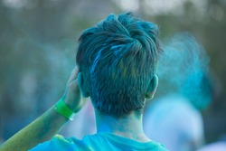 Young man with hair full of blue colored powder at color run festival, back view