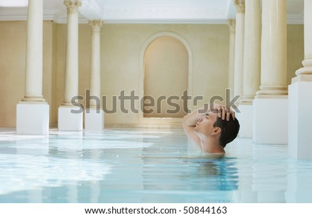 Young man with hand on head in swimming pool, side view