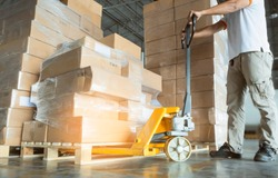 Young man with hand pallet truck or pallet jack and stack of cardboard boxes on pallet in distribution warehouse.