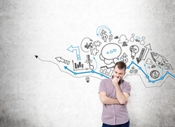young man with hand to the chin thinking and standing in front of a concrete wall with many different business icons drawn on it over a graph. Concept of business development.