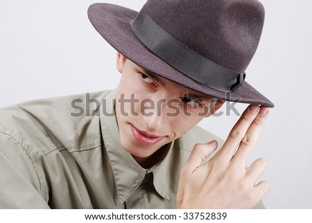 Young man with hat and two fingers pointed at