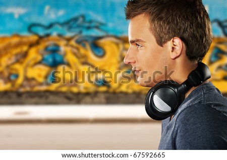 Young man with headphones against graffiti background