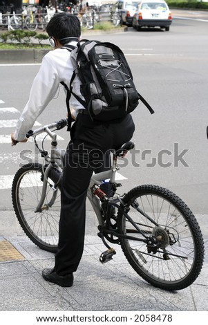 Young man with headphones and backpack riding a bicycle in a city.