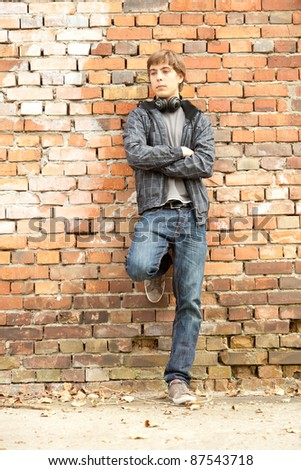 young man with headphones leaning on the old, bricks wall - stock photo
