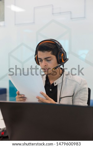 Young man with headphones, reading a document in coworking office.