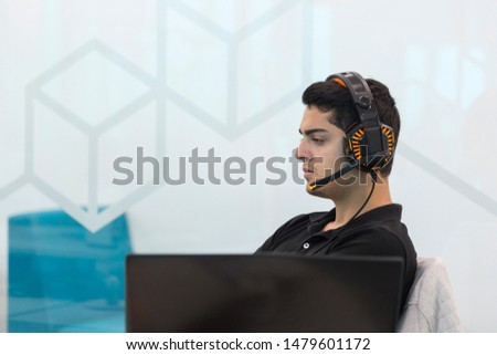 Young man with headphones, sitting in coworking office.