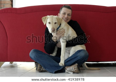 Young man with his dog ( Golden Retriever ), Focus on human face , red sofa in the background