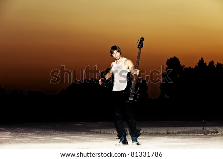 young man with his guitar at sunset, full body shot