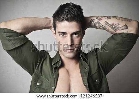 Young man, with his hands behind his head, showing the tattoo on his left forearm